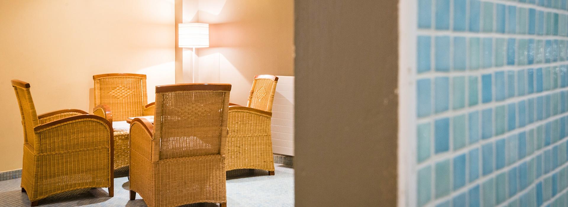 Salon de détente avec fauteuil en osier au jacuzzi de l'hôtel le Chalet à Ax les Thermes en Ariège